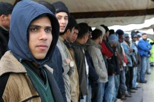 Would-be immigrants wait on arrival to L